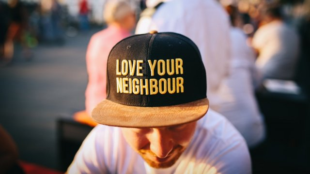 "A guy waering a cap that states ""Love your Neighbour"""